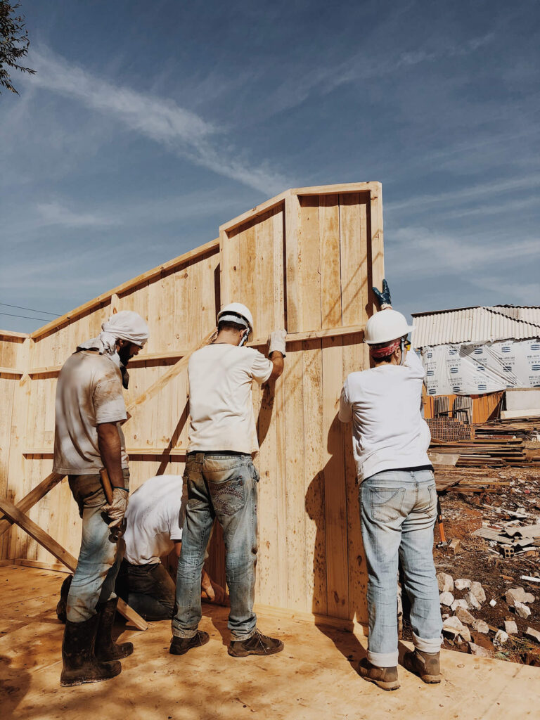 Three men in white t-shirts and jeans and white hardhats constructing a fence outside.