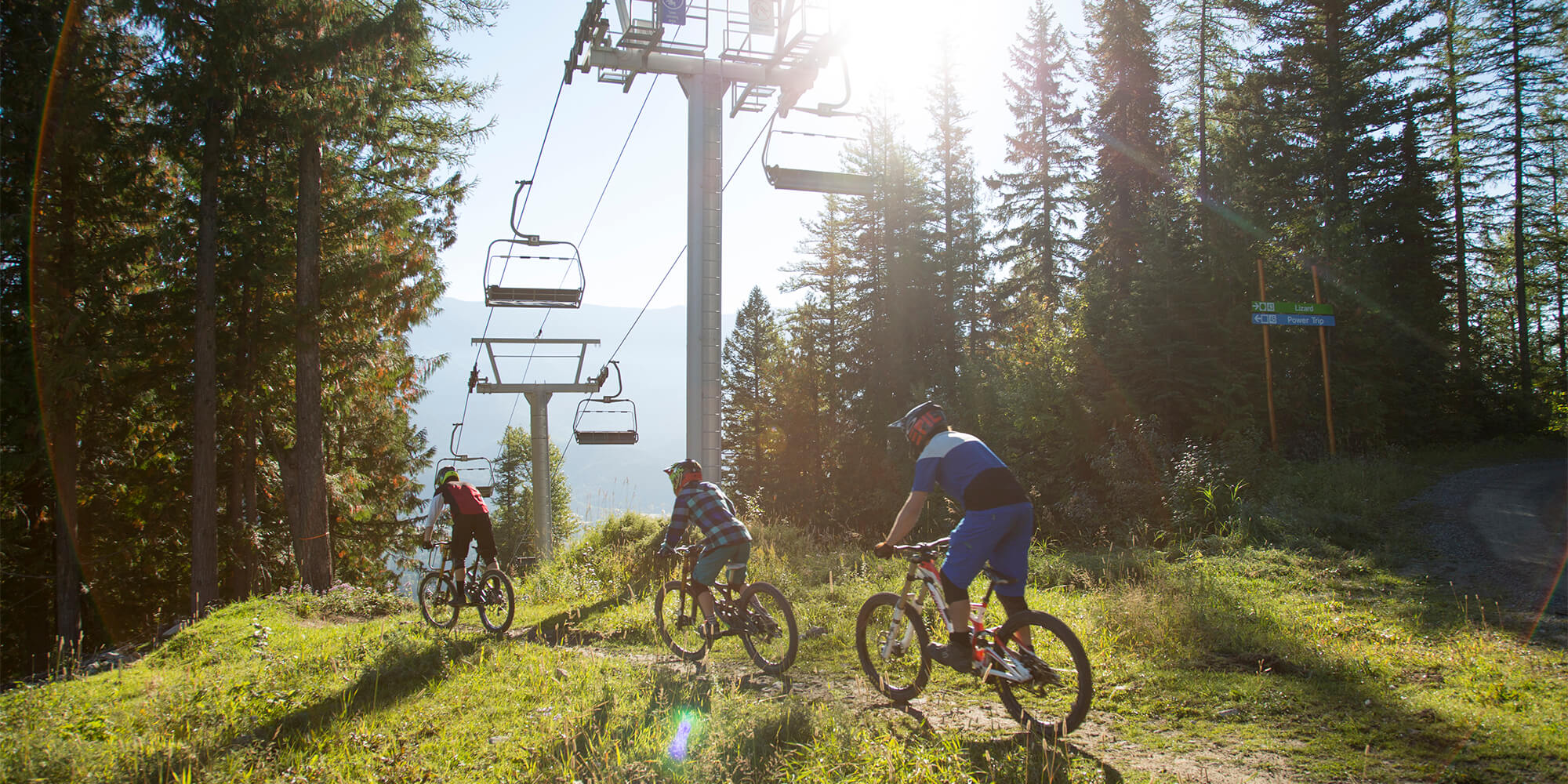 Three people on mountain bikes below a ski lift chair in the summertime in Fernie, BC.