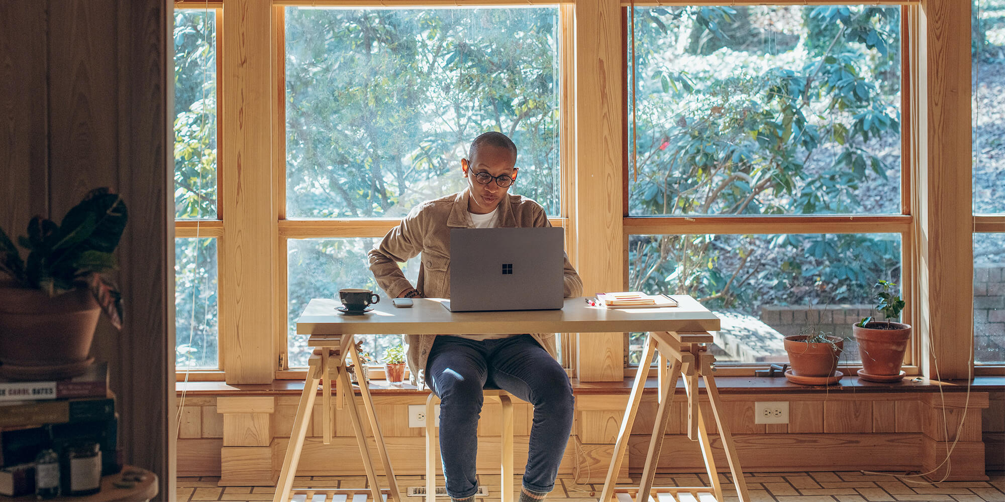 A man sits at a desk in front of a laptop, with open windows behind him revealing a forest.